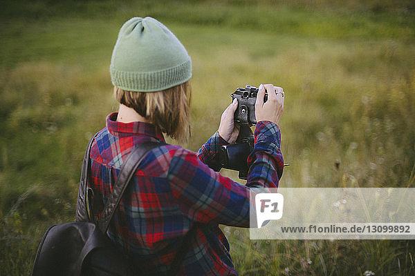 Seitenansicht einer Frau mit Rucksack beim Fotografieren im Stehen auf einem Grasfeld