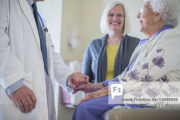 Male doctor holding hand and talking to female patient sitting by daughter in hospital ward