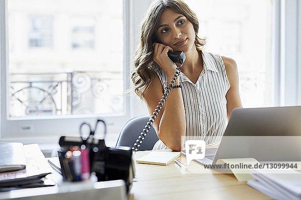 Geschäftsfrau,  die bei der Arbeit am Schreibtisch im Büro ans Telefon geht