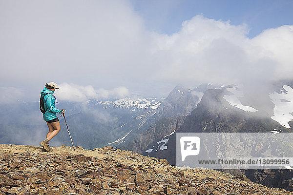 Seitenansicht einer Wanderin mit Wanderstock beim Wandern auf einem Berg vor bewölktem Himmel