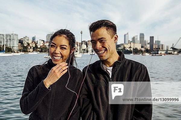 Glückliches junges Paar hört Musik  während es gegen das Stadtbild trainiert