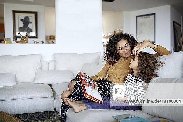 Mutter liest Bilderbuch für niedliche Tochter  während sie zu Hause auf dem Sofa sitzt