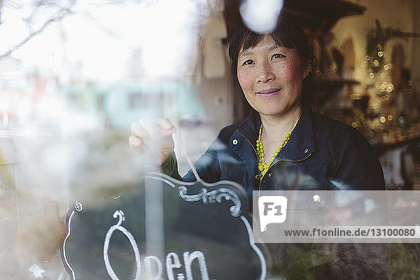 Weiblicher Eigentümer hängt offenes Schild am Fenster des Gartencenters durch Glas gesehen