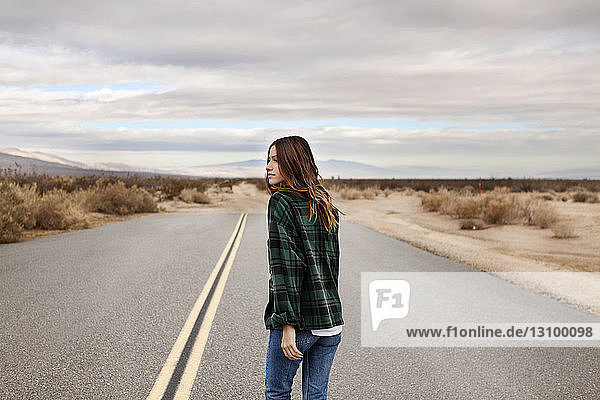 Rear view of thoughtful woman walking on country road