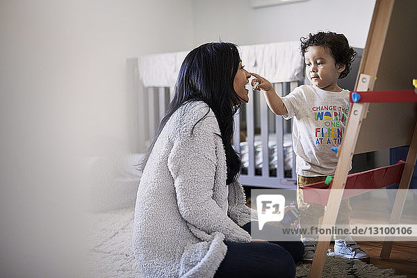 Cute playful son touching mother's nose while drawing on canvas at home