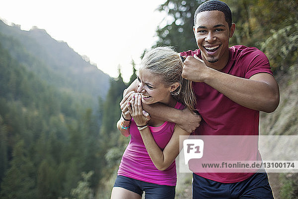 Porträt eines verspielten Joggers mit Frau am Berg