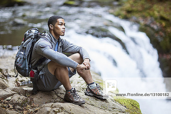 Thoughtful male hiker sitting on rock by waterfall