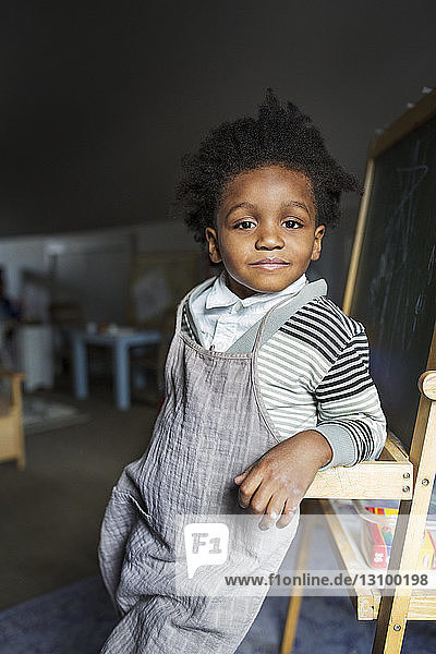 Portrait of confident boy leaning on blackboard at home