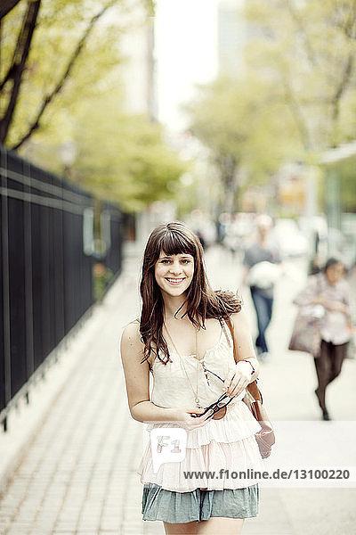 Porträt einer glücklichen Frau auf dem Bürgersteig stehend