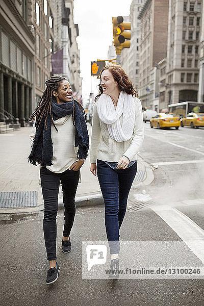 Fröhliche Frauen,  die sich beim Gehen auf der Straße von Angesicht zu Angesicht gegenüberstehen