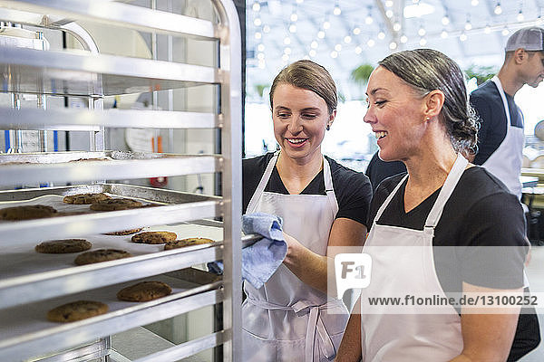 Female chefs examining cookies at restaurant kitchen