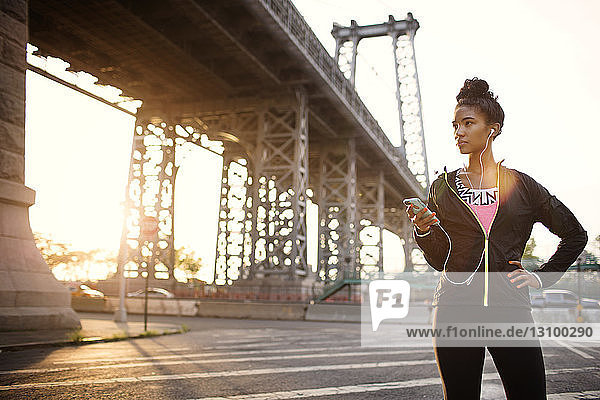 Woman listening to music through headphones while standing on city street