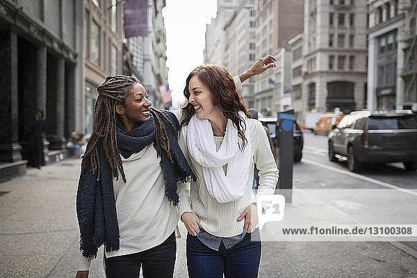 Freundinnen lächeln und genießen  während sie auf dem Fußweg stehen