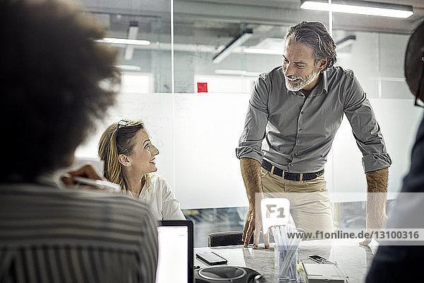 Männliche und weibliche Kollegen lächeln während der Besprechung im Büro