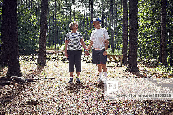 Senior couple holding hands while standing in forest