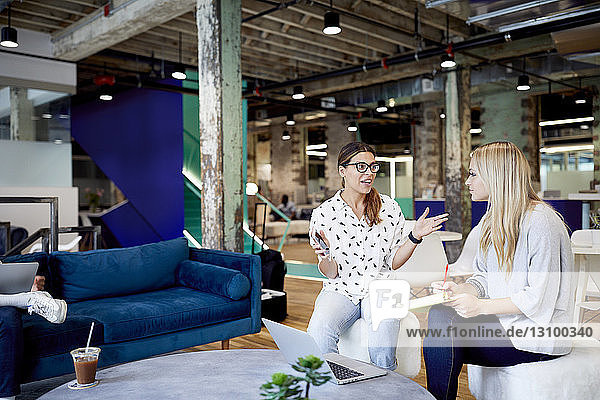 Businesswomen planning while using laptop at table in creative office