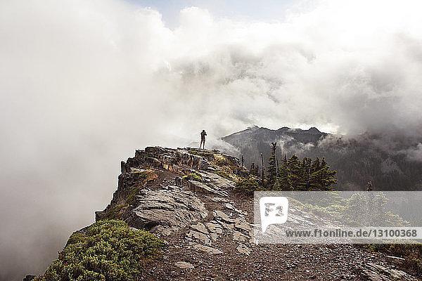 Mann steht auf Klippe vor bewölktem Himmel
