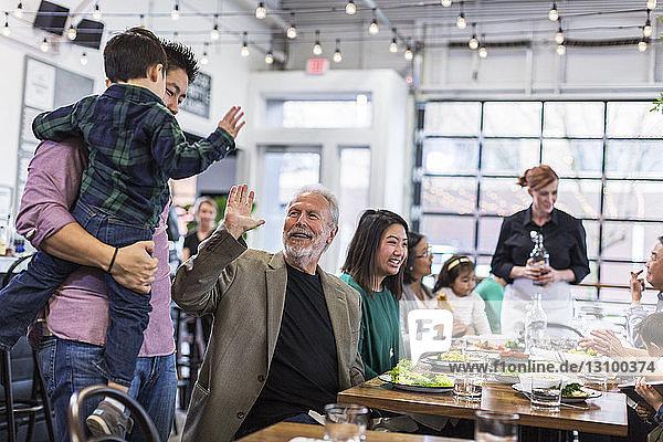 Kellnerin serviert glückliche Familie im Restaurant