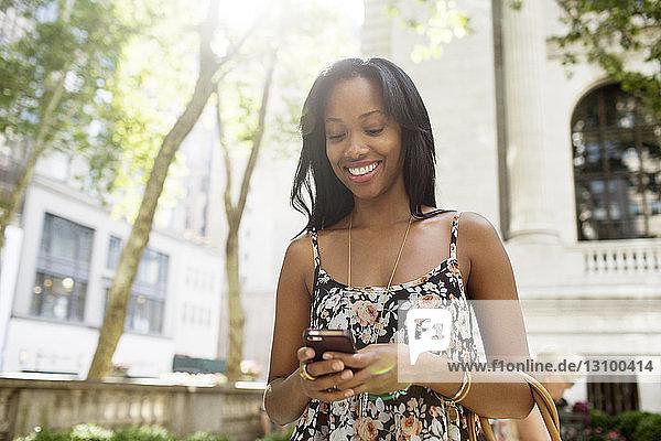 Glückliche Frau sendet Textnachrichten  während sie in der Stadt steht