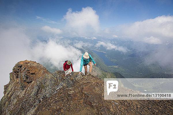 Hochwinkelansicht von Wanderern  die den Berg gegen einen bewölkten Himmel besteigen