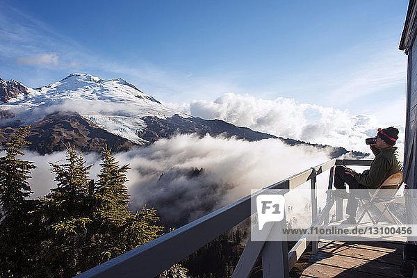 Mann sitzt auf Balkon und trinkt Kaffee gegen Berge