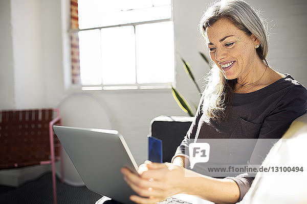 Happy woman using laptop while sitting on sofa in living room at home
