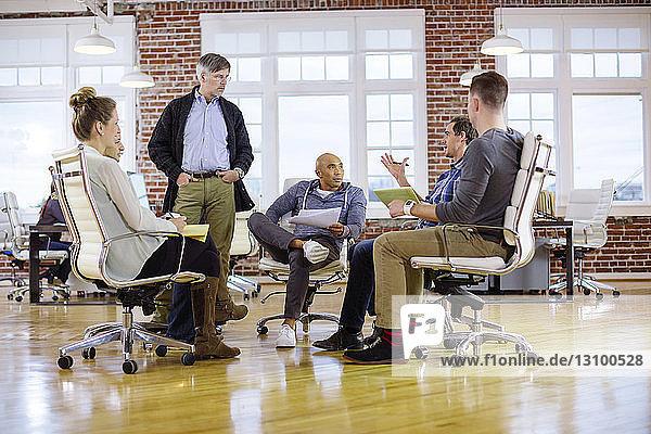 Geschäftsleute planen  während sie im Büro auf Stühlen sitzen