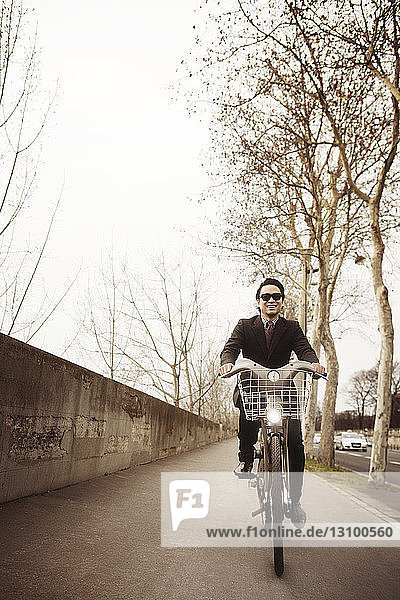 Front view of smiling man riding bicycle on street against clear sky