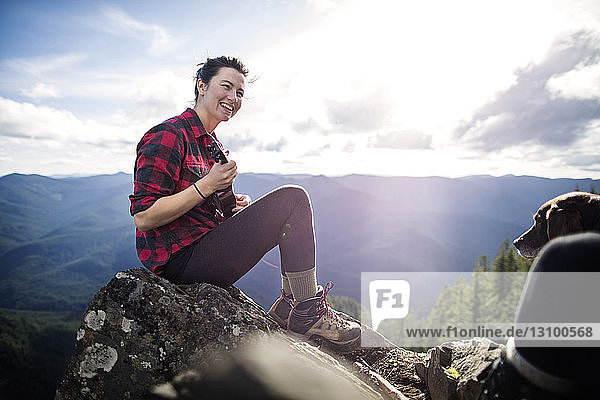 Woman playing ukelele while sitting on rock at mountain cliff