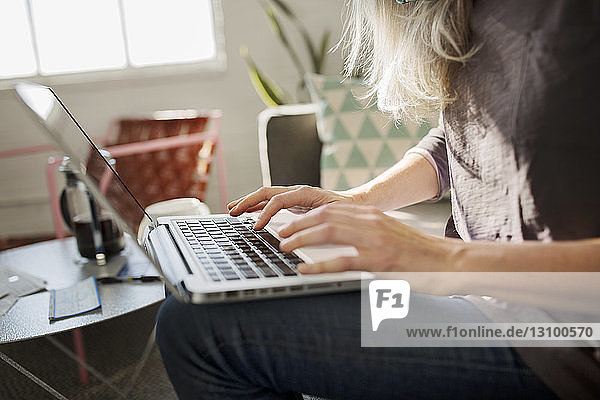 Midsection of woman using laptop in living room at home