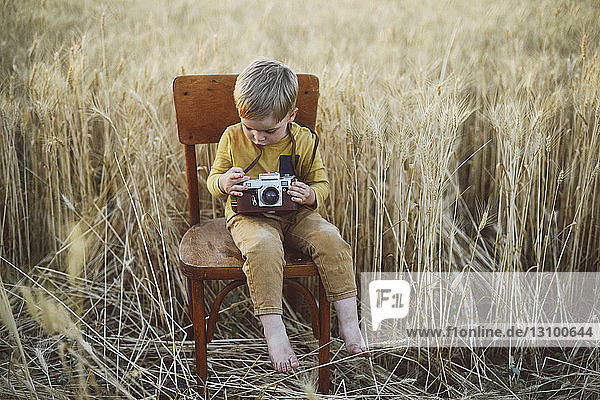 Full length of boy with vintage camera sitting on chair amidst wheat field
