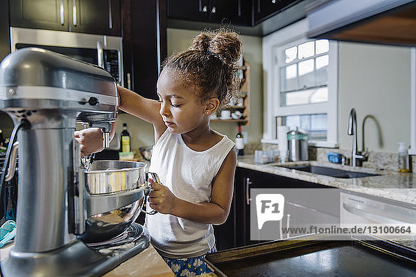 Girl preparing cookies in kitchen