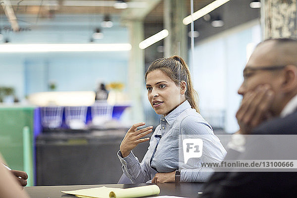 Businesswoman planning strategy with colleague in meeting at conference table