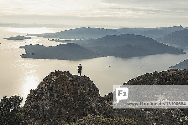 Hochwinkelaufnahme eines unbekümmerten Wanderers  der bei Sonnenuntergang auf einem Berg gegen den Himmel steht