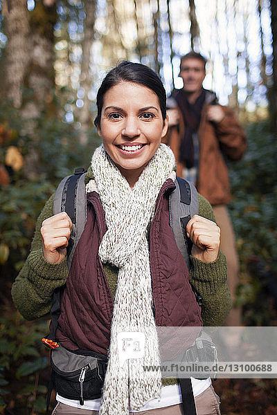 Porträt einer glücklichen Frau  die mit einem Mann im Wald wandert