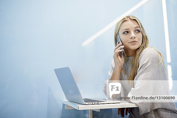 Businesswoman with laptop looking away while talking on mobile phone at creative office