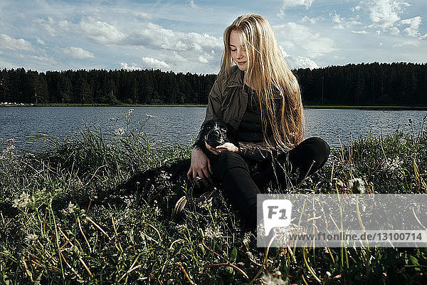 Woman sitting with dog by lake against cloudy sky