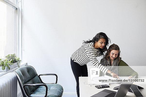Weibliche Kollegen  die bei der Arbeit im Sitzungssaal auf ein Buch schauen