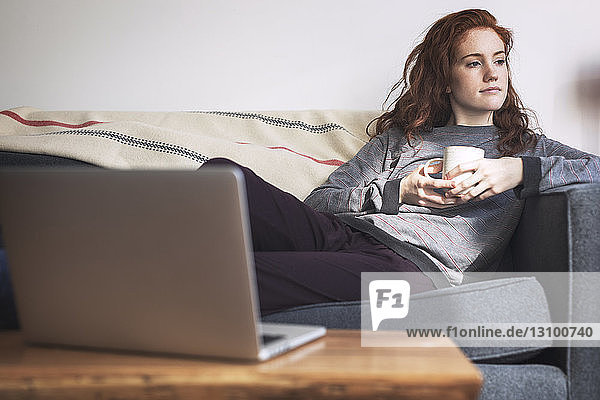 Thoughtful woman with coffee cup looking away while relaxing on sofa