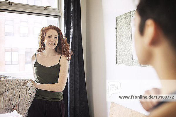 Playful lesbian with pillow looking at girlfriend while standing in bedroom