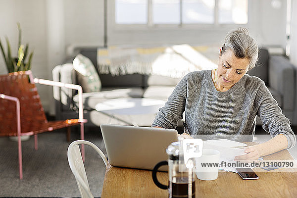 Concentrated woman writing on paper while working on laptop in living room