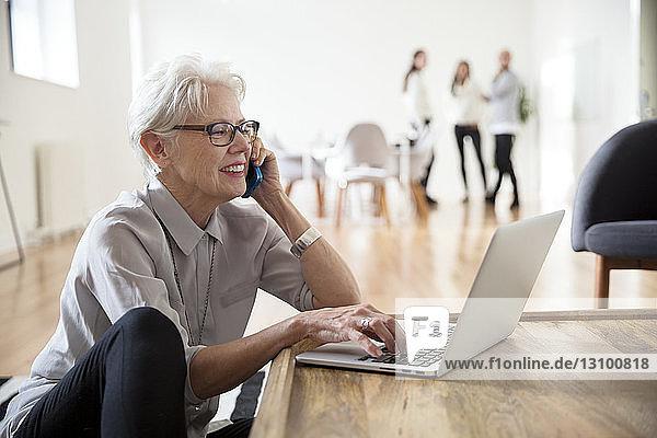 Leitende Geschäftsfrau  die mit dem Laptop telefoniert