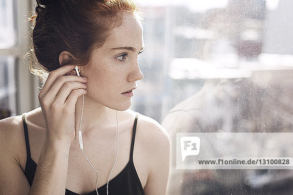 Thoughtful woman looking through window while listening music at home