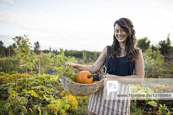 Porträt einer fröhlichen Frau  die Gemüse in einem Korb gegen den klaren Himmel im Gemeinschaftsgarten trägt Porträt einer fröhlichen Frau, die Gemüse in einem Korb gegen den klaren Himmel im Gemeinschaftsgarten trägt