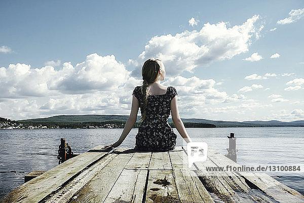 Nachdenkliche Frau sitzt am Pier über dem Fluss vor bewölktem Himmel