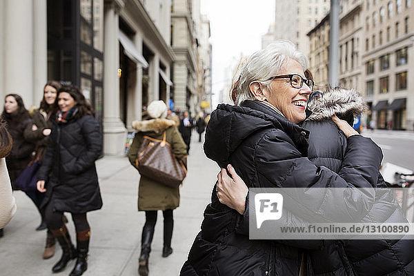 Fröhliche Frauen umarmen sich auf dem Fußweg in der Stadt