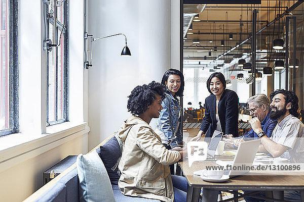 Fröhliche Geschäftsleute  die während einer Besprechung im Amt diskutieren