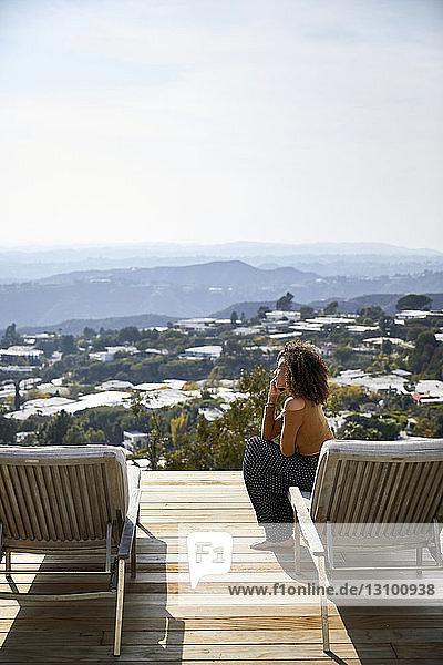 Seitenansicht einer Frau  die mit dem Handy telefoniert  während sie auf einem Liegestuhl gegen den Himmel sitzt
