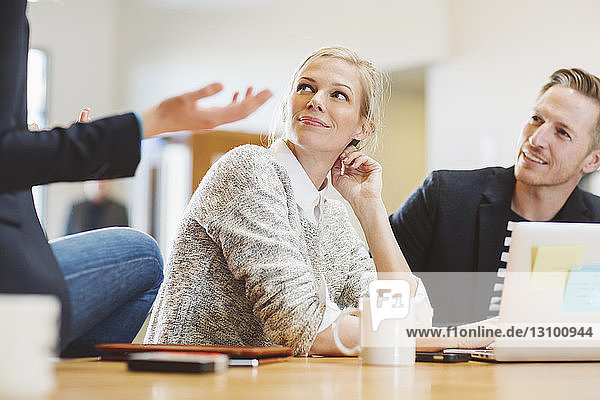 Colleagues looking at businesswoman talking while sitting on table in office