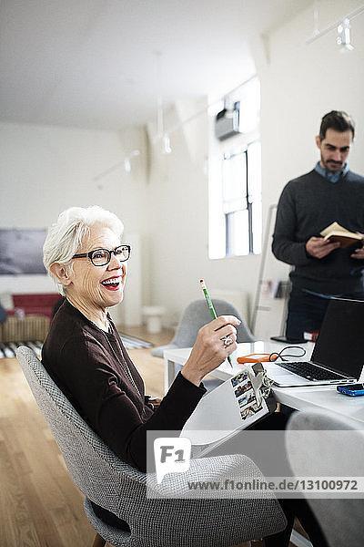 Lächelnde ältere Geschäftsfrau sitzt im Büro auf einem Stuhl